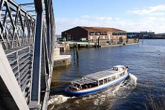 Barkasse unter der neugebauten Baakenbrücke - im Hintergrund ein Schiffsanleger mit Wassertreppe und Lagerschuppen am Baakenhafen.