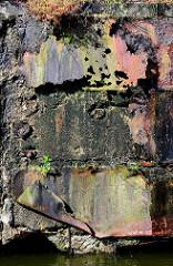 Farbig rostende Blechreste an einer Kaimauer im Hamburger Hafen.