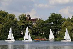 Blick über die Aussenalster zum Ufer an der Bellevue in Hamburg Winterhude - Segelboote kreuzen vor dem Ufer.