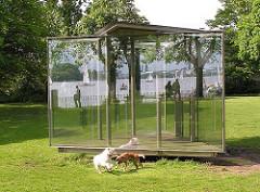 """Das begehbare Kunstwerk """"Double Triangular Pavillon For Hamburg"""" wurde 1989 vom Künstler Dan Graham geschaffen; es steht an der Stelle des ehemaligen Uhlenhorster Fährhaus.  Die Alster mit Spaziergängern und Segelboote spiegelt sich in der Glasin"""