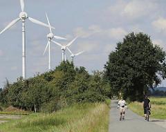 Windräder auf dem Lande - Energiegewinnung durch Windkraft. Fahrradfahren und Rollerscaten auf derm asphaltierten Strecke der ehem. Marschenbahn.