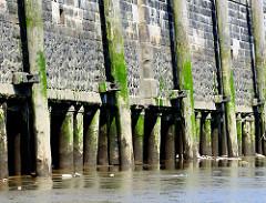 Kaimauer  im Hamburger Baakenhafen / Versmannkai bei Ebbe; die Kaianlage ist auf Holzstämmen gegründet - Streichdalben schützen die Wand / Schiffe beim Anlegen.