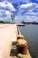 Eisenpoller zum Vertäuen von Frachtschiffen am Versmannkai des Baakenhafens - im Hintergrund ein hoher Hafenkran und Gebäude von Hamburg Rothenburgsort,