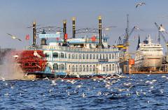 Fahrgastschiff der Hamburger Hafenrundfahrt - Schaufelraddampfer Louisiana Star im Hamburger Hafen - ein Schwarm Möwen umfliegen das Schiff - im Hintergrund liegt das Kreuzfahrtschiff Europa im Trockendock.