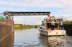 Geöffnetes Schleusentor der Krapphofschleuse am Schleusengraben von Hamburg Bergedorf - ein Sportboot verlässt die Schleusenkammer und fährt in den Schleusengraben ein.