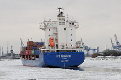 Container Feeder ICE RUNNER auf der Elbe - das Frachtschiff fährt durch das eisbedeckte Wasser des Hamburger Hafens.