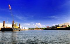 Blick in den Baakenhafen der Hamburger Hafencity - am Versmannkai liegt ein grosser Arbeitsponotn - rechts Lagerhallen am Petersenkai; im Hintergrund  ein Hochhaus in Hamburg Rothenburgsort.