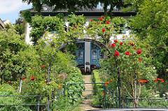 Wohnhaus am Strandweg von Hamburg Blankenese - Rosenbogen mit blühenden Rosen am Eingang.