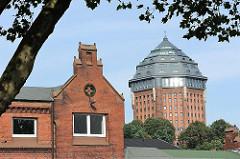 Industriearchitektur in Hamburg St. Pauli - Ziegelgiebel eines alten Schlachthofgebäudes in Hamburg St. Pauli - im Hintergrund der ehem. Wasserturm im Schanzenpark, der zum Hotel umgebaut wurde.