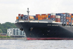Das 336m lange und 46m breite Containerschiff NYM ORPHEUS läuft aus dem Hamburger Hafen aus - im Hintergrund Bürogebäude am Ufer der Elbe in Hamburg Neumühlen.