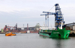 Der Frachter ARKLOW BRIDGE liegt unter der Förderanlage im Dradenauhafen - die Fracht wird über ein Förderband in das Aluminiumwerk transportiert.