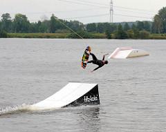 Absprungrampe der Wasserskianlage am Neuländer See - ein Wakeboarder springt ab - Bilder aus Hamburg Neuland.