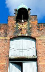 Winde auf dem Dach des Speicher G mit Kupferdach. Fassadenschmuck mit farbigen Ziegeln gemauer.