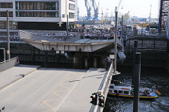 Klappbrücke über die Einfahrt vom Sandtorhafen in der Hafencity - die Brücke schliesst sich - eine Barkasse fährt in das Hafenbecken ein.