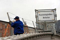 Auftrennen des Zollzauns an der Kannengiesserbrücke / Brook mit einer Flex - Funken sprühen; 2001 wird die der Hamburger Stadtteil Hafencity mit der Speicherstadt aus der Freizone / Freihafen ausgegliedert.