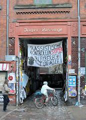 Architektur in Hamburg St. Pauli - Eingang Jäger-Passage in der Wohlwillstrasse; Transparent Rassistische Kontrollen stoppen Bleiberecht für Alle.