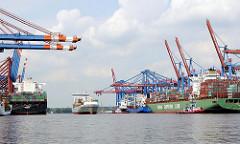 Schiffe im Waltershofer Hafen - ein Containerfeeder läuft in das Hafenbecken ein; ein Frachter wird auf die Ausfahrt aus dem Hamburge Hafen von Schleppern vorbereitet.