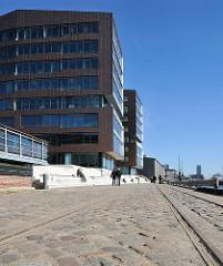Modernes Bürogebäude, Kopfsteinpflaster und Schienen der alten Hafenbahn in Altona.