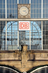 Glasfenster der Bahnhofshalle des Dammtorbahnhofs. Uhr und Logo der Deutschen Bahn DB.