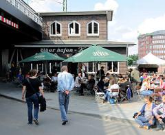 Oberhafenkantine - Gäste an Tischen in der Sonne unter Sonnenschirmen - das Gebäude wurde 1925 erricht und wurde als sogen. Kaffeeklappe für die Hamburger Hafenarbeiter genutzt.