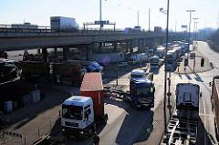 LKW mit Containern haben die Zollstation passiert und fahren in den Hamburger Freihafen ein. Darüber der Autoverkehr auf der Autobahn A7.