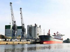 Kräne und ein Frachtschiff im Reiherstieg von Hamburg Wilhelmsburg - Bilder aus den Stadtteilen Hamburgs.