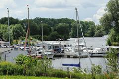 Sportboothafen am Ufer der Dove-Elbe im Hamburg Stadtteil Allermöhe; Motorboote und Segelboote liegen am Schlengel; im Hintergrund Bäume am Ufer der Doveelbe.