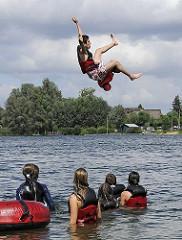 Wassersport am Oortkatener See - Jugendliche springen in das Wasser den Sees.  Wassersport in Hamburgs Naherholungsgebieten.