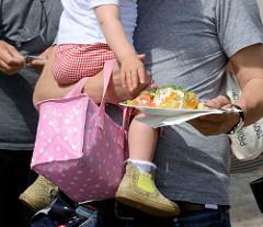 Biohof Gut Wulksfelde - Bauernmarkt. Aussteller präsentieren ihre Bioprodukte und Kunsthandwerk. Ein Vater trägt sein Kind mit Tasche auf dem Arm - es langt nach dem Essen auf dem Teller in der anderen Hand des Vaters.