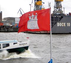 Die Hamburgfahne flattert im Wind - auf der Elbe vor den Landungsbrücken fährt eine Hafenfähre, im Hintergrund Werftanlagen + Dock 10.