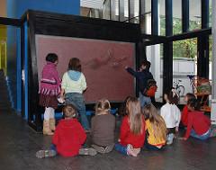 Kindermuseum Hamburg - Osdorf - eine Klasse sitzt vor einem Objekt im Museum.
