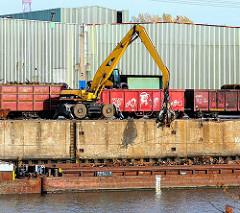 Die Ladung einer mit Schrott beladenen Schute wird mit einem Greifbagger gelöscht und in bereitstehende Güterwaggons verladen - Bilder aus dem Hamburger Stadtteil Waltershof.