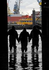 Sturmflut in Hamburg Altona - Wasser in der Fischauktionshalle - Arbeitskräfte gehen mit Gummistiefeln und Wathosen duch das Wasser - im Hintergrund legt eine Hafenfähre auf der Elbe.