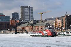 Winter in Hamburg - Eisgang auf der Elbe - eine Hafenfähre fährt zum Anleger Altona Fischmarkt.