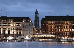 Nachtaufnahme von der Hamburger Binnenalster - beleuchtete Kaufhäuser am Jungfernstieg - Alsterpavillon, dahinter Grosse Bleichen mit Kirchturm der St. Michaeliskirche im Abendhimmel.