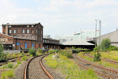 Historisches Bahnhofsgebäude und Lagerhallen des ehem. Güterbahnhofs Oberhafen in der Hafencity Hamburg - im Hintergrund die moderne Architektur des Spiegelgebäudes am Oberhafenkanal.