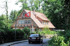 Fachwerkgebäude mit Ziegeln eingedeckt - Hamburg Fahne im Vorgarten. Bilder aus dem Stadtteil Hamburg Rönneburg.