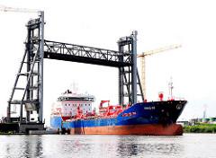 Für das Tankschiff ICDAS 09 wird die Rethehubbrücke angehoben - der 150m lange Tanker fährt hindurch - Fotos aus dem Hafengebiet von Hamburg Wilhelmsburg.