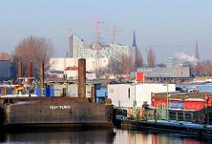 Blick über den Travehafen in Hamburg Steinwerder - Arbeitsschiffe und Schuten liegen am Ponton; am Heck eines grossen Lastkahns ist der Heimathafen Hamburg angebracht - im Hintergrund die Baustelle der Albphilharmonie.