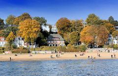 Sonniger Herbstnachmittag am Elbststrand von Hamburg Othmarschen; bunt gefärbte herbstliche Bäume am Elbhang - Spaziergänger am Strand; Häuser an der Promenade.