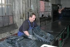Ein Arbeiter legt die Platten mit Hartgummi-Rohlingen zur Fertigstellung der Kämme bereit / Betriebsstätte der New-York Hamburger Gummi-Waaren Compagnie Aktiengesellschaft in Hamburg Harburg.