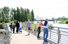 Fussgänger auf der Hakenbrücke - einige blicken auf die Elbe bei Hamburg Rothenburgsort - im Hintergrund Pappeln des Elbparks.