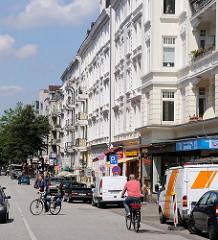 Fahrradfahrer und parkende Autos im Mühlenkamp - Gründerzeitarchitektur in Hamburg Winterhude.