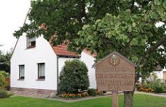 Geschnitztes Holzschild Siedlergemeinschaft AM RADELAND e.V. Die Eigenheimgemeinschaft entstand 1933 als Erwerbslosensiedlung.