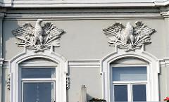 Fassadendekor über den Fenstern eines Wohngebäudes - Stuckadler an der Hausfassade - beschädigtes Dekor, kopfloser Adler.