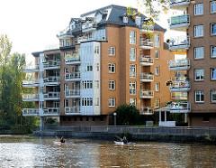 Wohngebäude / Wohnanlage am Ufer der kanalisierten Alster in Hamburg Eppendorf - Paddler paddeln auf dem Wasser des Hamburger Flusses.