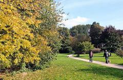 Grünanlage + Spaziergänger am Ufer der Wandse in Hamburg Eilbek - Bäume mit herbstlich gelben Blättern.