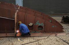Ein Werftarbeiter schweisst Schiffssegmente in der Arbeitshalle zusammen.