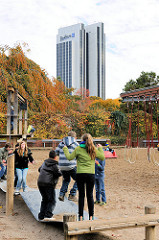 Kinderspielplatz in Planten un Blomen - Herbstbäume und Hamburger Radisson Blue Hotel - höchstes Haus der Hansestadt Hamburg mit 120m.