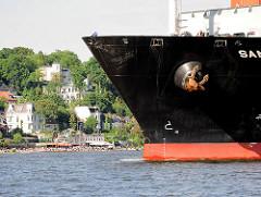 Frachter beim Auslaufen aus dem Hamburger Hafen - Schiffsbug; im Hintergrund Häuser und Elbstrand / Strandperle in Hamburg Othmarschen.